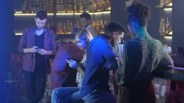 Thumbnail for Indifferent Friends Using Phones at Bar Counter