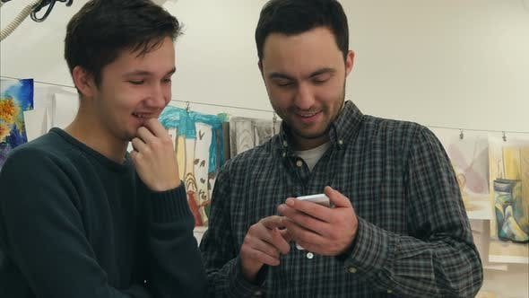 Thumbnail for Two Positive Art Students Laughing at Something on the Phone