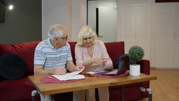 Senior Couple Checking Calculating Bills Bank Loan Payment Doing Paperwork Discuss Unpaid Debt Taxes