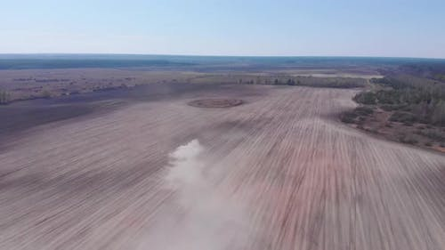 Combine plows land. Dust in field. Aerial view of tractor in field.