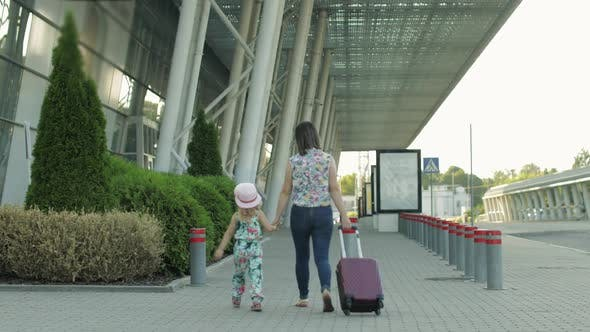 Thumbnail for Mother and Daughter Walking To Airport. Woman Carrying Suitcase Bag. Child and Mom Vacation. Rear