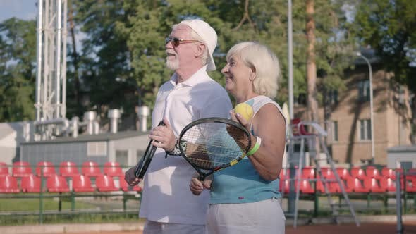 Thumbnail for Cute Smiling Mature Couple for Getting Ready To Play Tennis on the Tennis Court