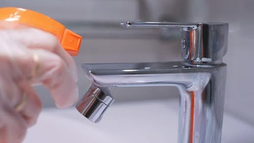 Close-up of a Spray of Cleaning Agent on a Chrome Faucet in the Bathroom. Hygiene, House Cleaning