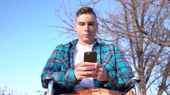 Cover Image for Young Man on a Wheelchair with a Phone. Disabled Man in Nature Is in Correspondence on a Smartphone.