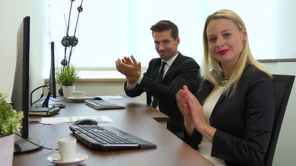 Thumbnail for Two office workers, man and woman, work on computers, then smile at the camera and applaud