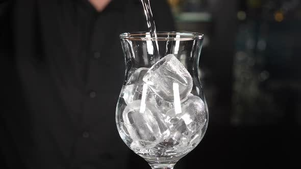 Thumbnail for Bartender Making Cocktail Pouring Transparent Alcohol Liquid Into Glass with Ice Cubes