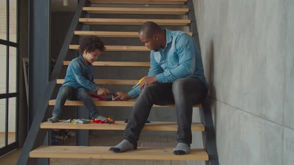 Cover Image for Cute Kid with Dad Playing with Toy Tools on Stairs