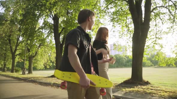Cheerful Teenage Couple Strolling in Sunlight in Summer Park at Sunset Talking and Laughing