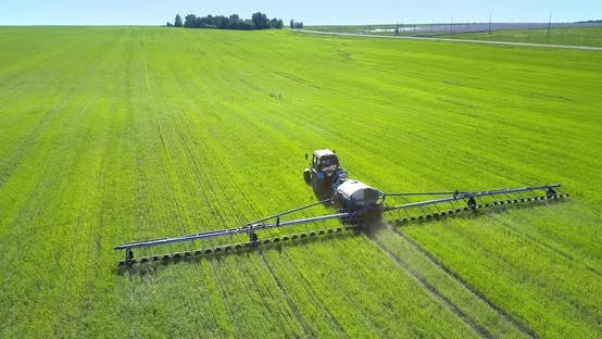 Thumbnail for Backside Tractor Field Sprayer Drives on Field To Wood