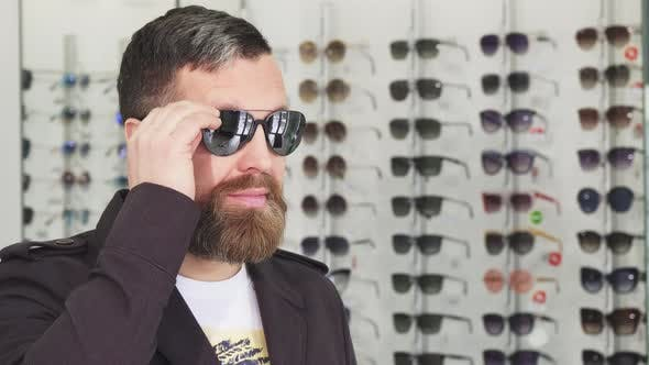 Mature Man Trying on Sunglasses at the Opticians Store