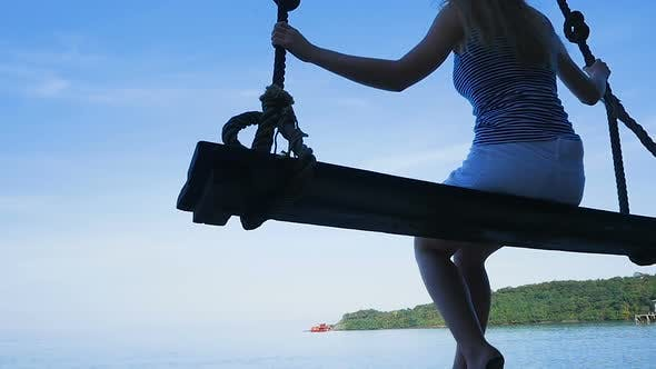 Thumbnail for Girl Sits on a Swing By the Sea. Thailand. Koh Kood