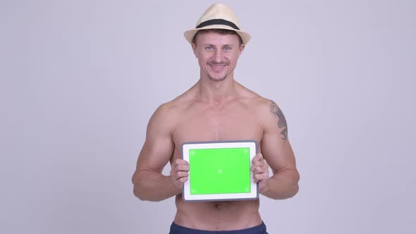 Thumbnail for Happy Muscular Bearded Tourist Man Showing Digital Tablet Shirtless