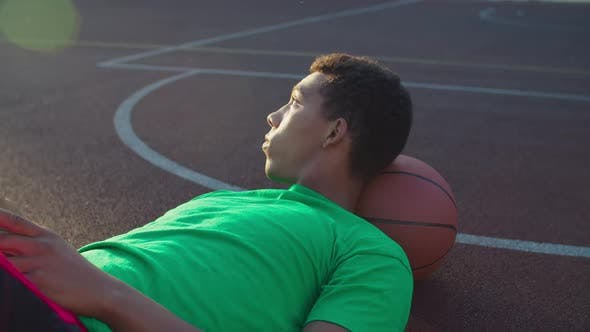 Basketball Player with Phone Resting After Training