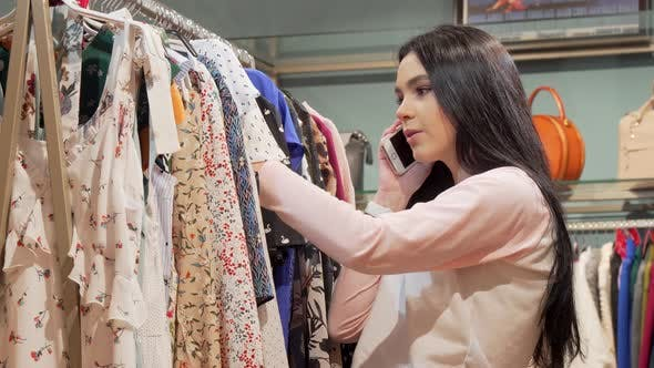 Thumbnail for Charming Young Woman Talking on the Phone While Shopping for Clothes