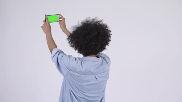 Cover Image for Rear View of Young Happy African Woman Taking Picture with Phone