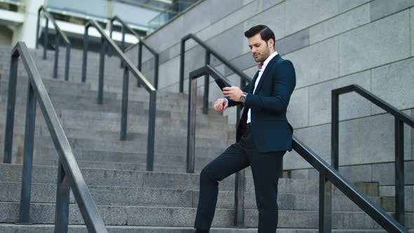 Cover Image for Businessman Laughing with Phone in Hand at Street. Man Using Smartphone Outdoor