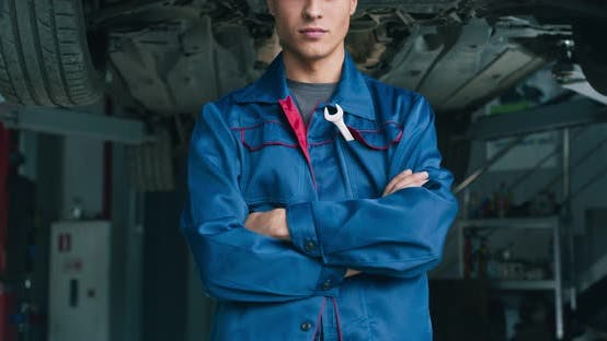 Young Confident Mechanic, Looking Seriously at Camera with Folded Arms, Garage Background