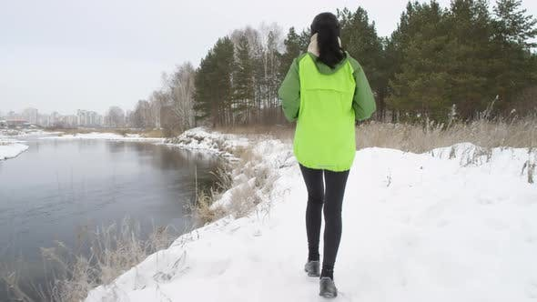 Thumbnail for Woman Jogging by Pond in Winter