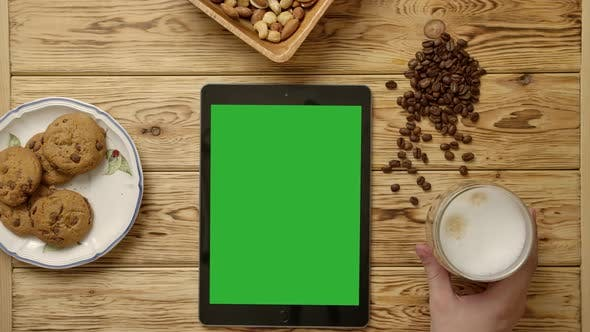 Thumbnail for Crop Nervous Person Eating Cookie Near Tablet and Breakfast Food