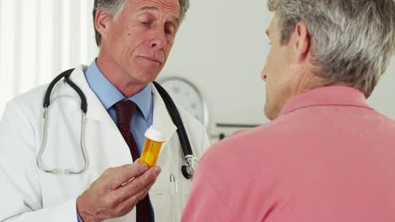 Senior doctor talking to elderly patient about prescription