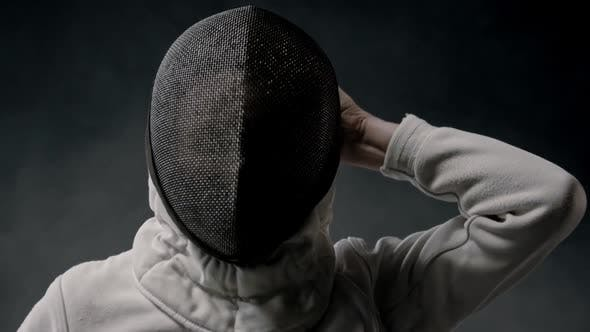 Fencing Training in the Dark Studio - Young Woman Putting on a Helmet and Stands in the Position