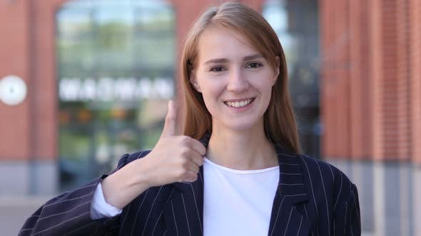 Thumbnail for Thumbs Up by Businesswoman at Work Looking at Camera