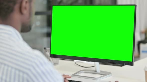 Rear View of African Man Using Desktop with Green Chroma Key Screen