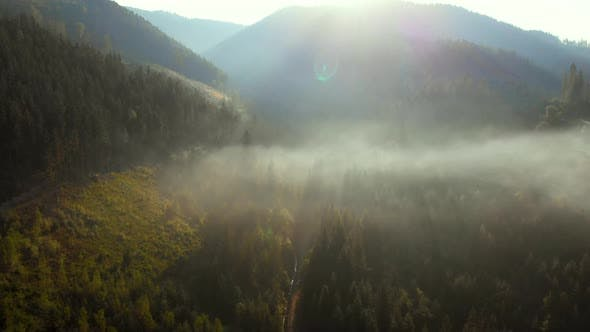 Aerial view of sunrise over foggy village in mountains.