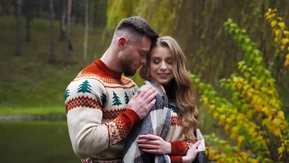 Young man hugged and covered girl with blanket. Beautiful couple outside. Autumn nature background.