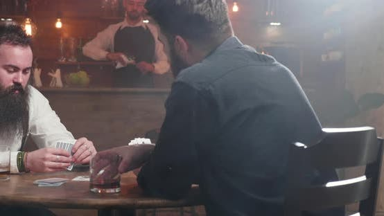 Thumbnail for Slide Shot From Right To Left of Two Young Man in a Bar Playing Cards