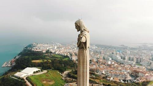 Majestic Jesus Stone Monument Against Almada City and Sky