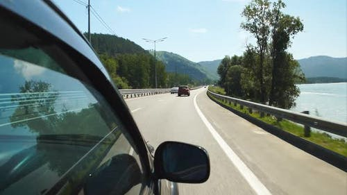 Car is moving along the Katun river on a highway in Altay, Russia