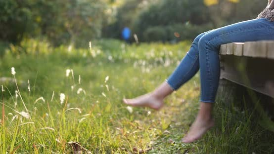 Thumbnail for Woman sitting on the wooden walking path and swing the legs
