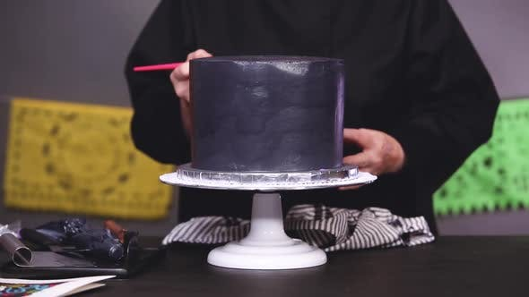 Thumbnail for Step by step. Baker applying glittery dust with brush to a black multilayer cake.
