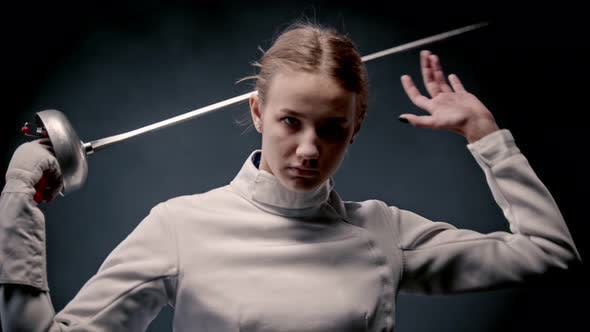 Thumbnail for Fencing Training - A Young Woman Fencer Walking Out From the Dark and Putting the Sword Behind Her