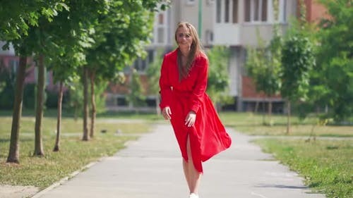 Happy young woman in the street. Beautiful young lady in passionate red dress