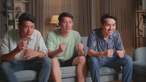 Asian Males Cheering And Watching Football Game On Tv At Home