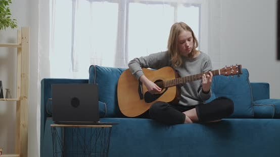 The Teenager Sits on a Soft Sofa