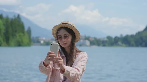 Asian Woman is Photographing Herself By Cell Phone in Nature in Slovenia