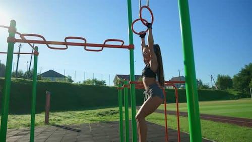 Muscular Girl Hanging Off Gymnastic Rings Raising Legs Up