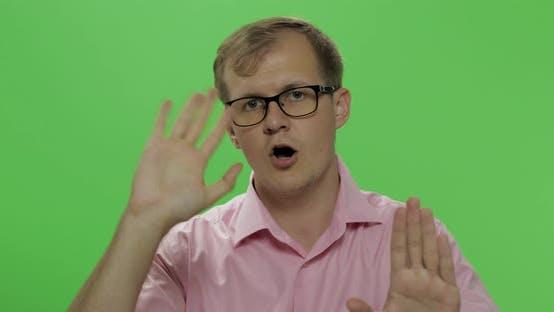 Thumbnail for Schüchtern junger Mann im Hemd winkt seine Hände und versucht, die Aufmerksamkeit auf ihn zu zahlen
