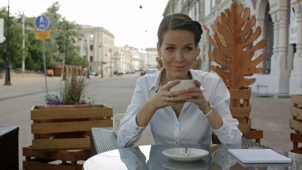 Thumbnail for Woman Drinking a Coffee From a Cup in a Restaurant Terrace While Thinking and Looking Sideways