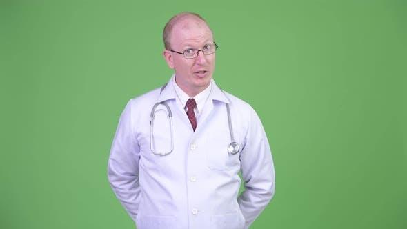 Thumbnail for Mature Bald Man Doctor Talking To Camera Explaining Something