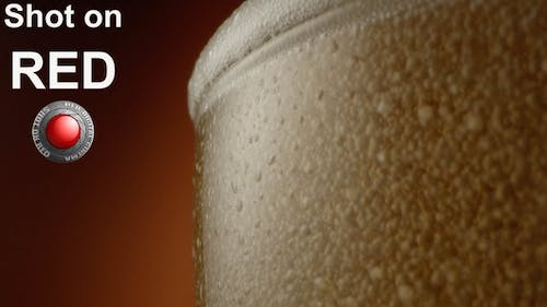 Froth Beer Pouring Out From A Glass A Macro Shot On Red Epic With Terra Cotta Background