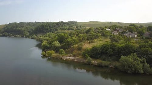 Aerial view of a small village in rural area between green trees on the shore of a big lake.