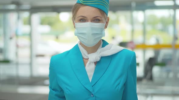 Thumbnail for Young Stewardess in Uniform and Face Mask Looking at Camera and Smiling. Portrait of Positive