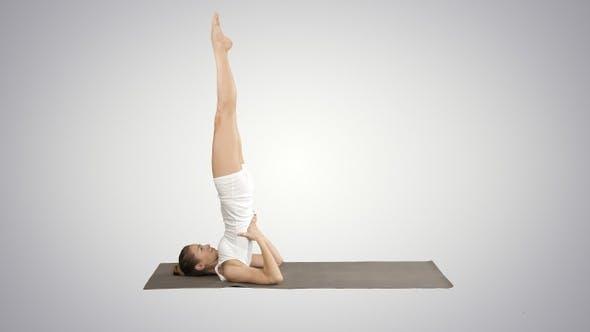 Thumbnail for Woman practicing yoga standing in salamba sarvangasana