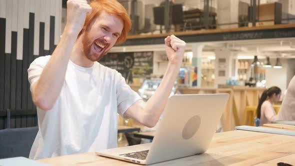 Thumbnail for Beard Man Celebrating Success, Sitting in Cafe