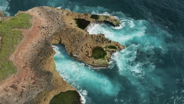 Thumbnail for Aerial drone view of powerful ocean waves breaking into a rocky coastline