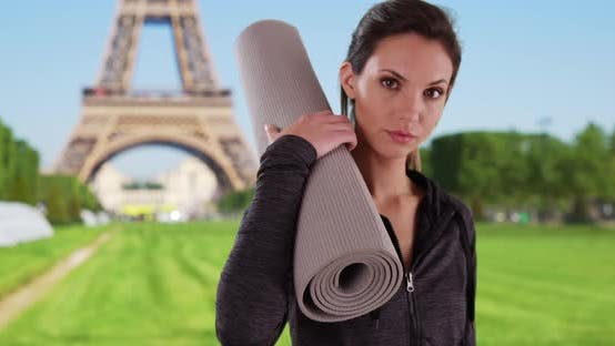 Thumbnail for Portrait of active woman holding yoga mat over shoulder by Eiffel Tower in Paris